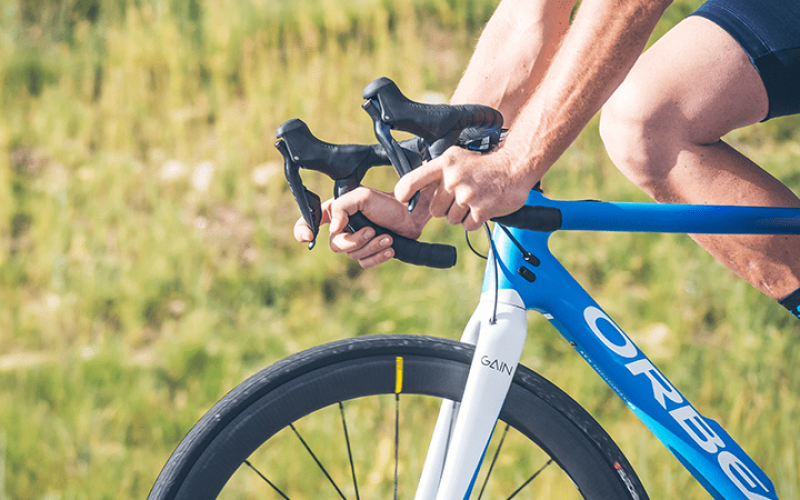 lifestyle image of a bicycle and a man gripping the handlebars