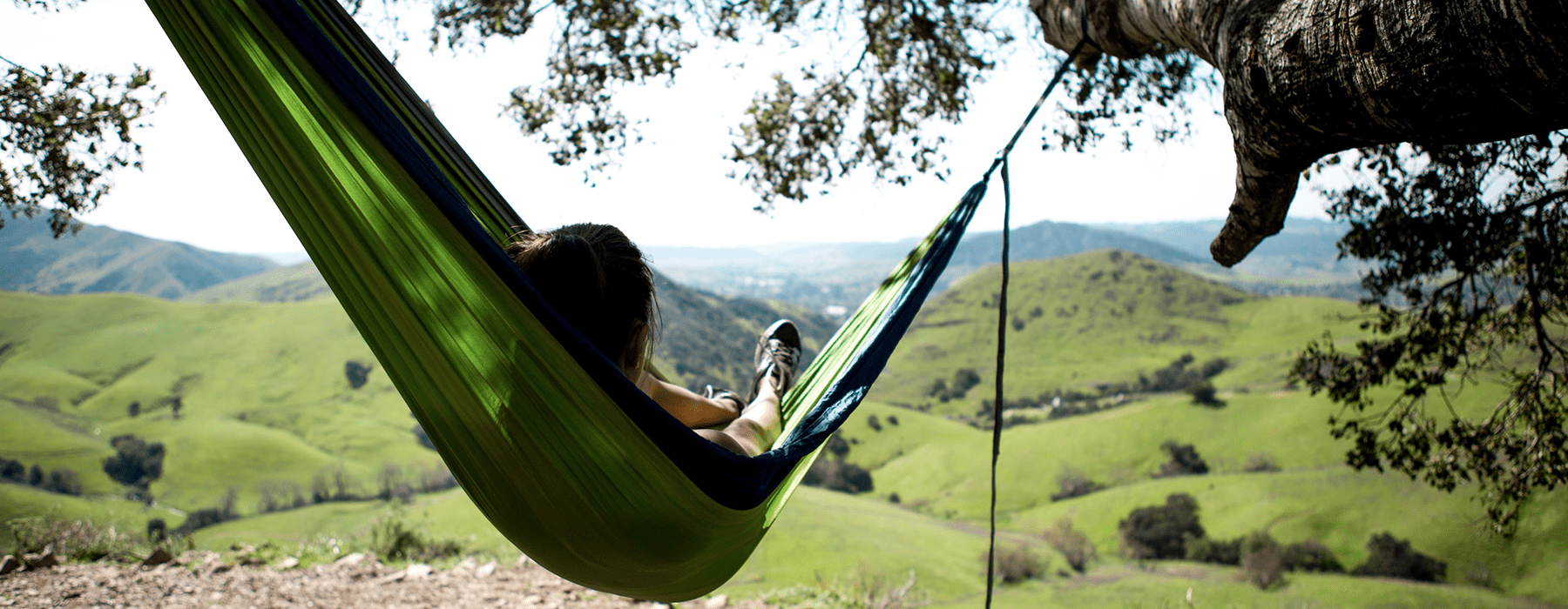 lifestyle image of a person relaxing in a hammock between two trees outdoors